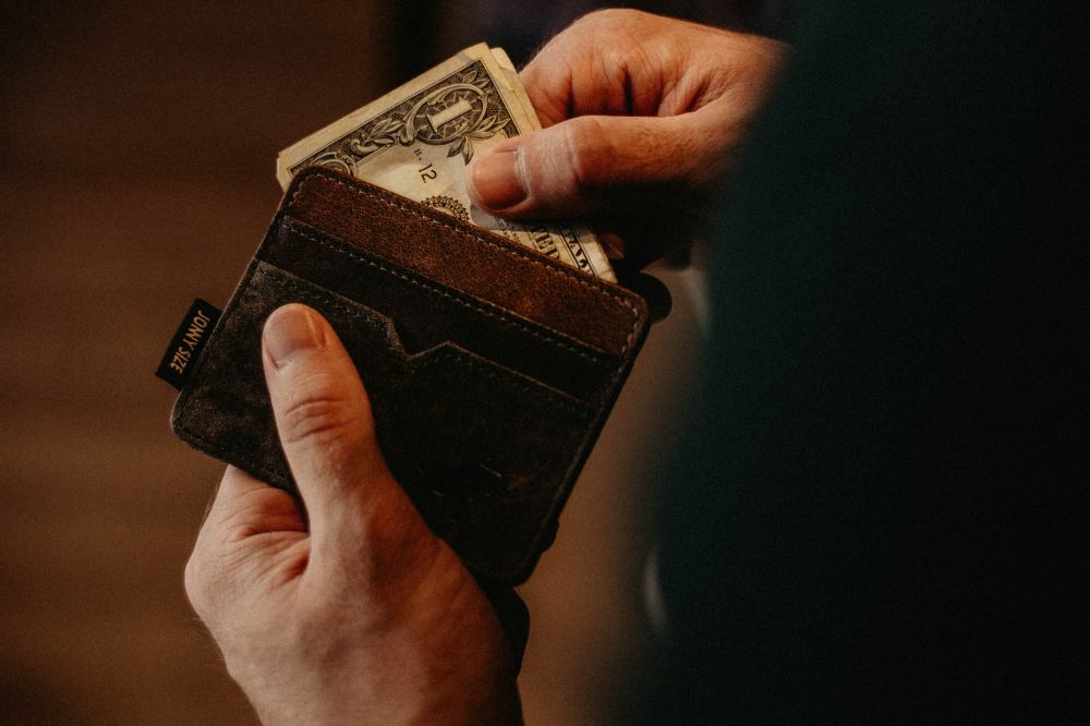 Picture of man inserting money in his wallet