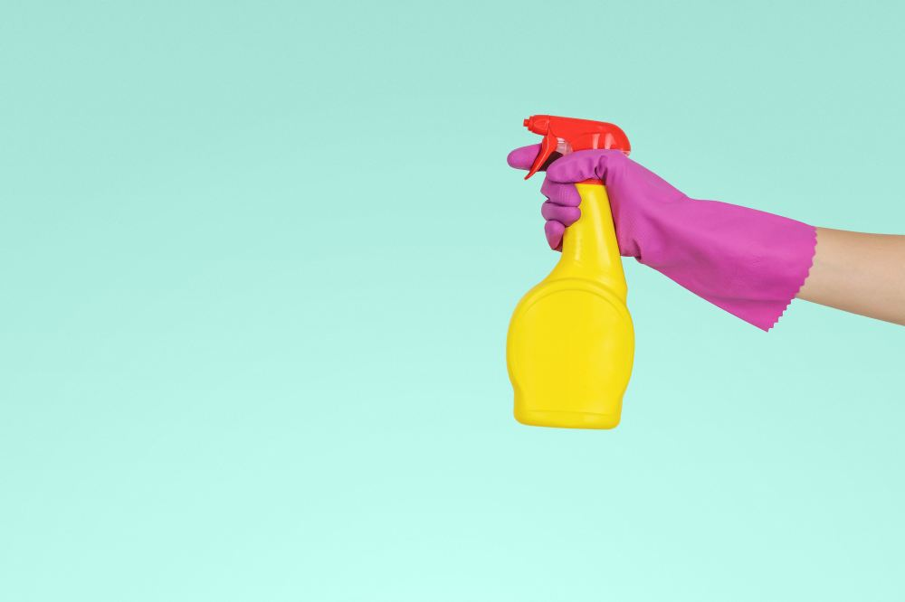 Image of a female hand holding a cleaning detergent